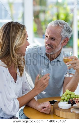 Mature couple smiling while holding wineglass at restaurant