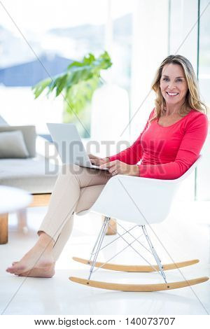 Portrait of happy woman using laptop while relaxing on rocking chair at home
