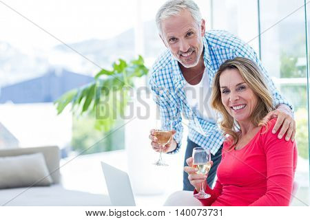 Portrait of happy couple with wineglass at home