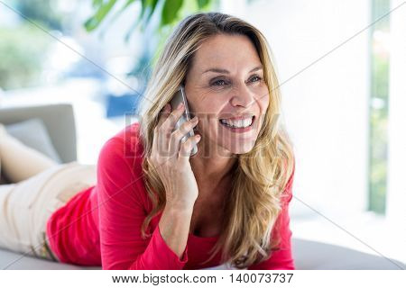 Beautiful woman smiling while talking on cellphone on sofa at home