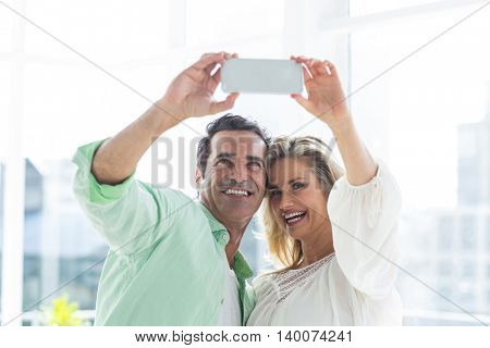 Cheerful couple taking selfie on smartphone at home