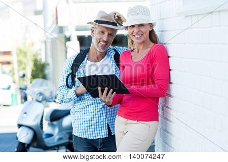 Portrait of happy mature couple with notepad standing by wall