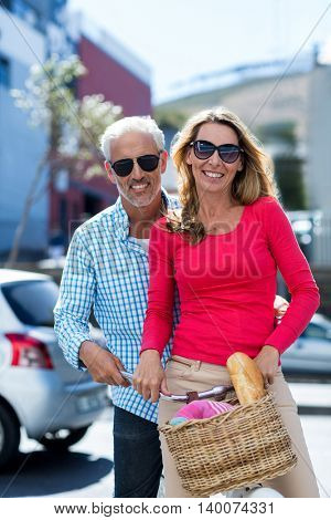 Portrait of happy mature couple riding bicycle on city street