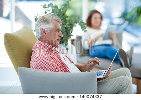 Mature man using laptop while woman relaxing in background at restaurant