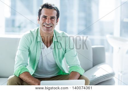 Portrait of man using laptop while sitting on sofa at home