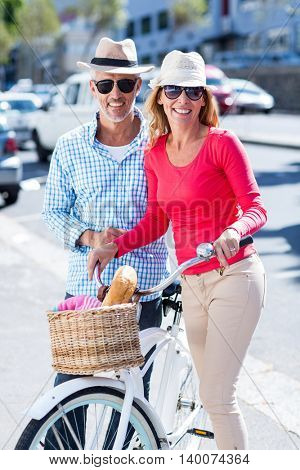 Portrait of smiling mature couple with bicycle on city street
