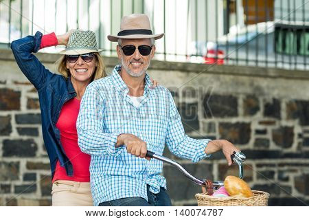 Portrait of happy mature couple riding bicycle against surrounding wall