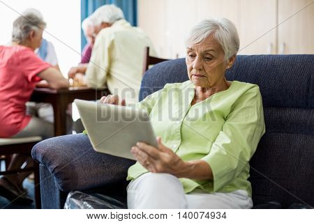 Senior woman using a tablet in a retirement home
