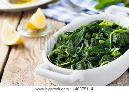 Boiled wild herbs Vlito with lemon juice and olive oil. The traditional Greek snack. Selective focus.