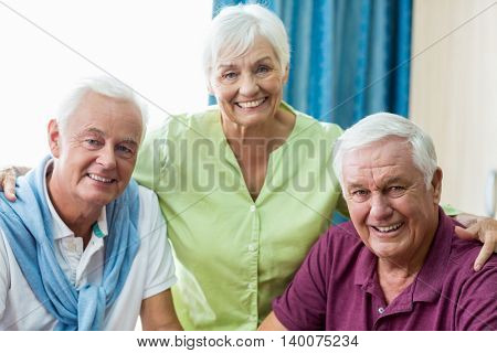 Seniors smiling at camera in a retirement home