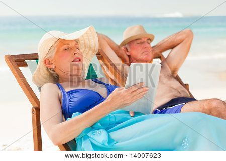 Woman Reading A Book While Her Husband Is Sleeping At The Beach