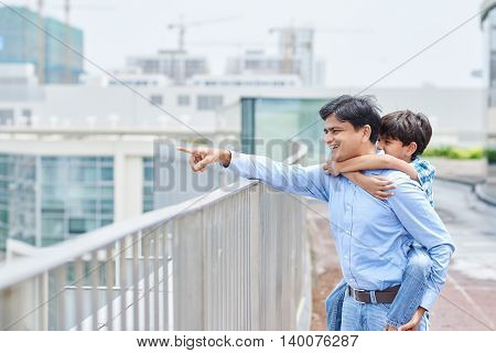 Indian father and son enjoying view from the bridge