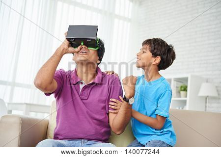 Indian man using VR giggles when his son sitting next to him