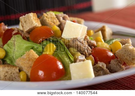 Tuna salad with tomatoes feta cheese corn and greens on plate