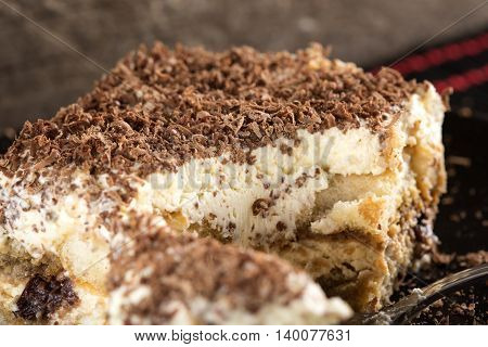 Tiramisu cake on dark plate with wooden background