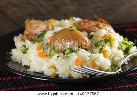 A plate of rice with fried chicken and vegetables. Selective focus.