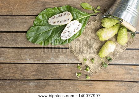 Noni fruit in tank on wooden table.Fruit for health and herb for health.