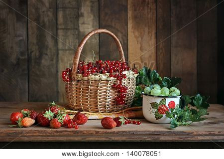 Still life with berries in a rustic style. Red currant gooseberry strawberries .
