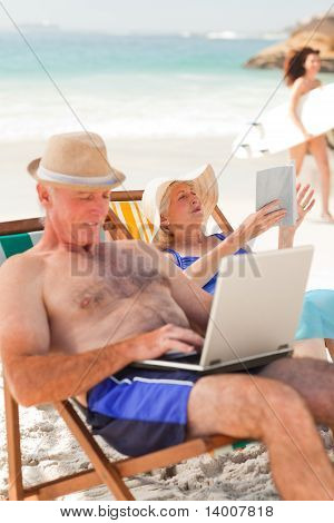Man Working On His Laptop While His Wife Is Reading At The Beach