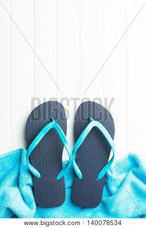 Blue flip flops with towel.