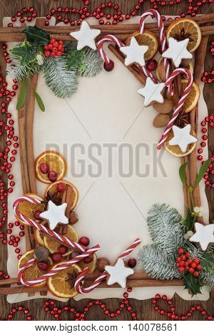 Christmas abstract background border with cinnamon sticks, candy canes, spices, gingerbread biscuits, fruit, nuts, red beads with holly and winter greenery parchment paper over oak wood.