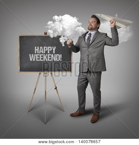 Happy weekend text on blackboard with businessman and paper plane