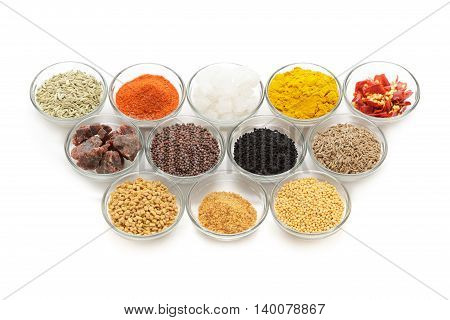 Different types of Indian spices in glass bowls isolated on white background. Elevated view.