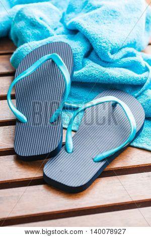 Blue flip flops with towel on wooden floor.