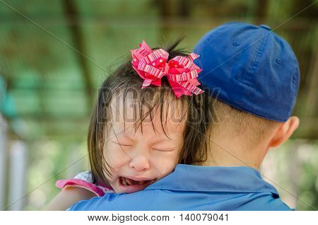 Little Asian girl crying on her father shoulder
