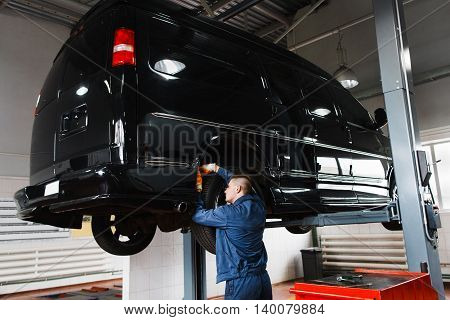 Black minibus on repair in garage. Mechanic working with SUV, lifted on elevator at modern auto service station
