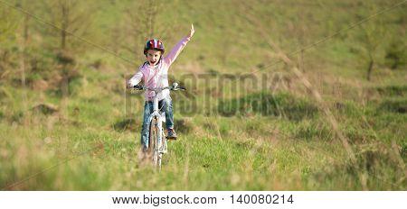 smiling little girl riding a bike in helmet