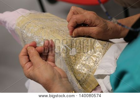 Hands Of The Elderly While Embroidering A Lace