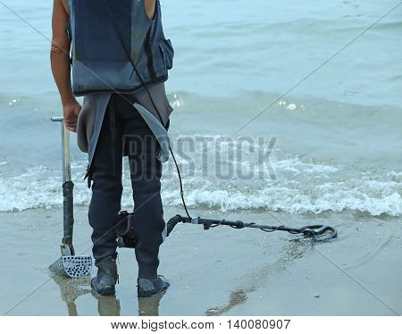 Man With Metal Detector On The Beach To Find Lost Objects Under