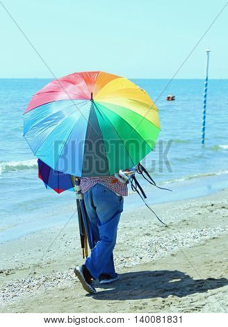 Peddler Of Umbrellas On The Beach