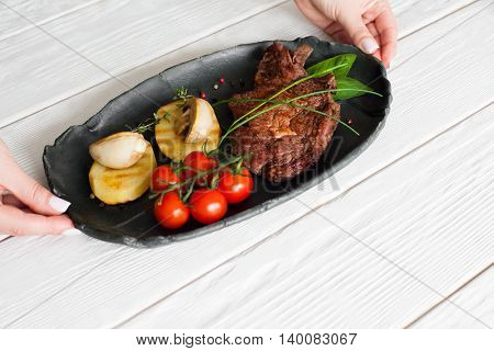 Hands put plate with steak and vegetables on white table, copyspace. Dining at restaurant, prepared food serving