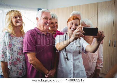 Retired people taking a selfie with a nurse in a retirement home