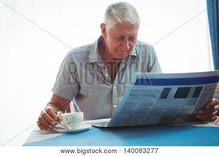 Retired man reading the news while holding a cup of tea at home