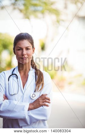 Portrait of a nurse with a serious look and arms crossed outside