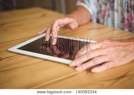 Old person touching a digital tablet on a table