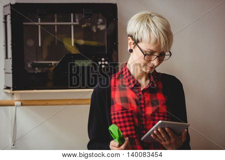 Portrait of female graphic designer holding model while using digital tablet at office