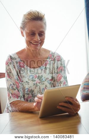 Portrait of smiling senior woman using a digital tablet