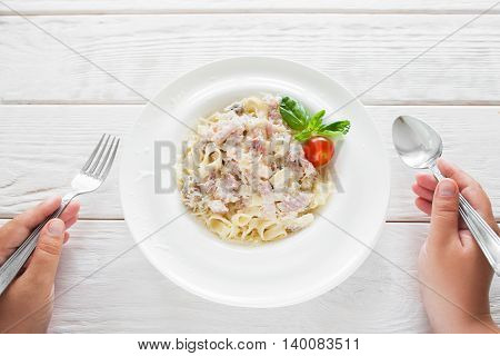 Spaghetti carbonara eating with fork and spoon, eater pov, flat lay. Dining at national Italian restaurant, noodles with bacon plate on white wooden table