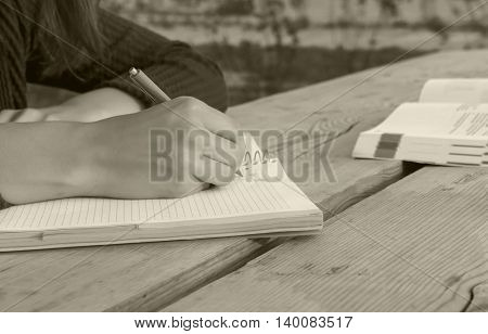 girl sits at a large wooden table and writes in a notebook, close the book, which develops wind sheets, black and white photo,