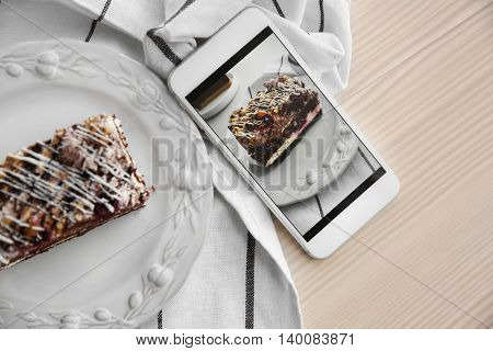 Cellphone with chocolate cake. Food blog concept