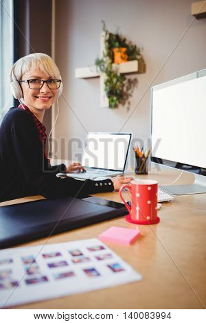 Portrait of female graphic designer working on computer and laptop at office