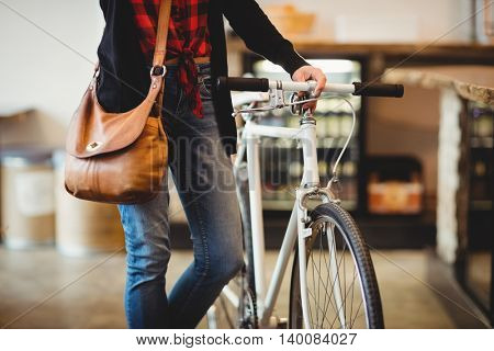 Mid section of woman standing along with bicycle at office cafeteria