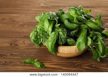 Fresh bunch of basil on wooden table