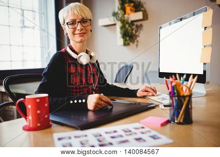 Portrait of female graphic designer using graphic tablet while working on computer at office