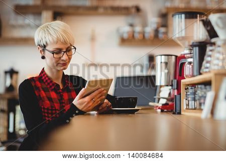 Young woman using digital tablet while having coffee at office cafeteria