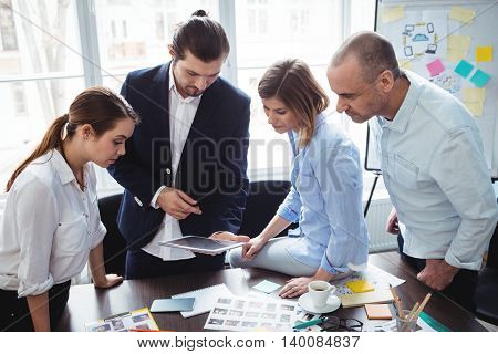 Photo editors using digital tablet while discussing in meeting room at creative office